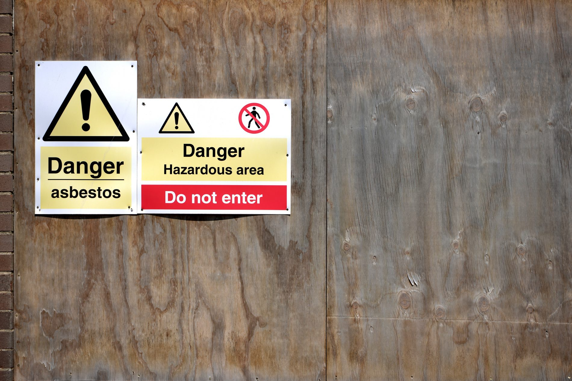 Danger asbestos sign on boarded up building